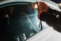 Male carjacker trying to open car door with ruler Royalty Free Stock Photo