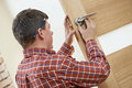 Male carpenter at lock installation worker handyman into wood door Royalty Free Stock Images