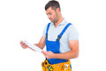 Male carpenter in overalls reading clipboard Royalty Free Stock Photo