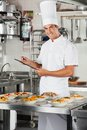 Male chef with clipboard at kitchen portrait of happy holding pasta dishes on commercial counter Royalty Free Stock Photos