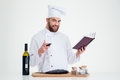 Male chef cook holding recipe book and glass with red wine portrait of a happy on a white background Royalty Free Stock Photos