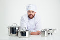 Male chef cook sitting at the table with dishes portrait of a happy on a white background Stock Images