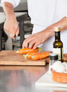 Male chef cutting carrots midsection of chopping on board in kitchen Stock Photos