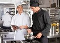 Male chef digital tablet assisting colleague preparing food kitchen Stock Photography
