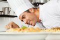 Male chef garnishing dish happy in commercial kitchen Royalty Free Stock Photo