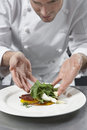 Male chef preparing salad in kitchen closeup of a Stock Image