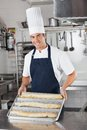 Male chef presenting baked bread loafs portrait of young in commercial kitchen Royalty Free Stock Photo
