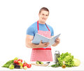 A male chef reading a cookbook while preparing a salad isolated on white background Royalty Free Stock Photography
