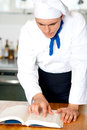 Male chef referring to cooking manual the ingredients of a recipe Royalty Free Stock Photography