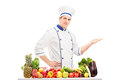 Male chef in a uniform gesturing with hand and posing behind a table full of fruits and vegetables isolated on white background Royalty Free Stock Photography
