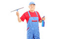 Male cleaner in uniform holding a cleaning equipment for glass isolated on white background Stock Photo