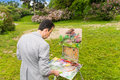 Male concentrated middle-aged creative painter mixing paint on Royalty Free Stock Photo