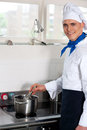 Male cook prepares a dish in the kitchen cheerful chef cooking hotel Royalty Free Stock Image