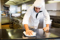 Male cook wiping the kitchen counter Royalty Free Stock Photo