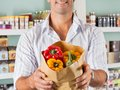 Male customer showing bellpeppers in paper bag midsection of at supermarket Royalty Free Stock Photo