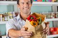 Male customer showing bellpeppers in paper bag portrait of mid adult at supermarket Royalty Free Stock Photo