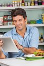 Male customer with snacks using digital tablet in portrait of mid adult at table grocery store Stock Images
