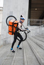 Male cyclist with courier bag and bicycle walking side view of on shoulder up steps Royalty Free Stock Photos