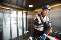 Male cyclist with courier bag using mobile phone young delivery in an elevator Royalty Free Stock Images