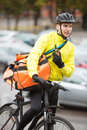 Male cyclist with courier bag using walkie talkie young delivery on street Royalty Free Stock Photography