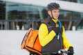 Male cyclist with courier delivery bag using young in protective gear walkie talkie Stock Image