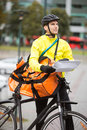 Male cyclist with package young in protective gear and courier bag on street Royalty Free Stock Photos