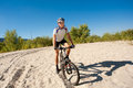Male cyclist riding bike stopped rolling sand clear summer day Stock Photo