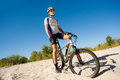 Male cyclist riding bike stopped rolling sand clear summer day Stock Photos