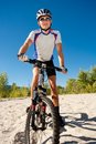Male cyclist riding bike stopped rolling sand clear summer day Stock Image