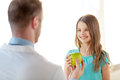 Male doctor giving an apple to smiling little girl Royalty Free Stock Photo