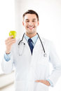 Male doctor with green apple bright picture of Stock Photos