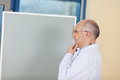 Male doctor with hand on chin standing by flipchart thoughtful mature in clinic Royalty Free Stock Images