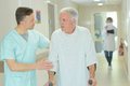Male doctor helping older patient with crutches Royalty Free Stock Photo