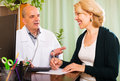 Male doctor talking with smiling mature patient in clinic office Royalty Free Stock Photo