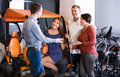 Male employee helping family to select tour electrics kindly at rental agency Stock Photography