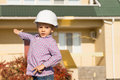 Male engineer kid showing architectural house close up in white helmet an at his back while looking at the camera Royalty Free Stock Image