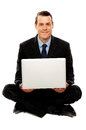 Male executive with laptop sitting on the floor Royalty Free Stock Photos