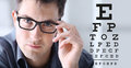 Male face with spectacles on eyesight test chart background