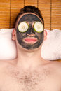 Male facial mask skincare man face with beauty treatment and cucumber laying on bamboo at spa Stock Photography