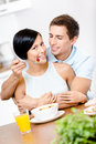 Male feeds and hugs his girlfriend man embraces sitting at the kitchen table concept of tasty dieting food Royalty Free Stock Photos