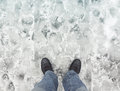Male feet in new shoes stand on wet dirty snow leather snowy road first person view Royalty Free Stock Image