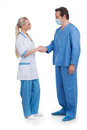 Male and female doctors shaking hands standing full length over white background Stock Photo