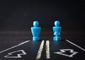 Male and female figurines on two way road Royalty Free Stock Photo