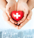 Male and female hands with red heart family health charity medicine concept holding cross sign Stock Image