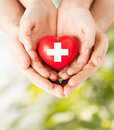 Male and female hands with red heart family health charity medicine concept holding cross sign Royalty Free Stock Photography
