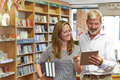 Male and female owners of bookstore using digital tablet Royalty Free Stock Photography