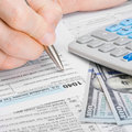 Male filling out united states of america tax form to ratio Royalty Free Stock Photo