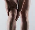 Male foot pain knee spasm or injury young man touching his sore leg Royalty Free Stock Photos