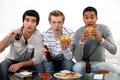 Male friends eating burgers and watching sport on tv Stock Photo