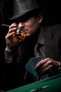 Male gambler playing poker drinking whiskey and smokes a cigar Royalty Free Stock Photography